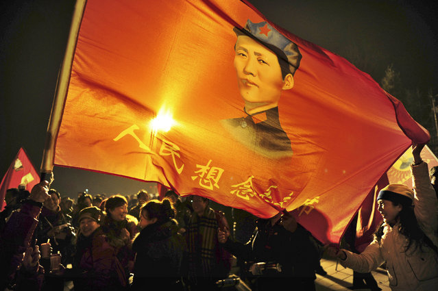 """Supporters wave a flag bearing an image of Chairman Mao Zedong and a slogan which reads """"People missing Chairman Mao"""", on the 120th birth anniversary of the former leader, in Shaoshan, Mao's hometown, December 25, 2013. (Photo by Reuters/Stringer)"""
