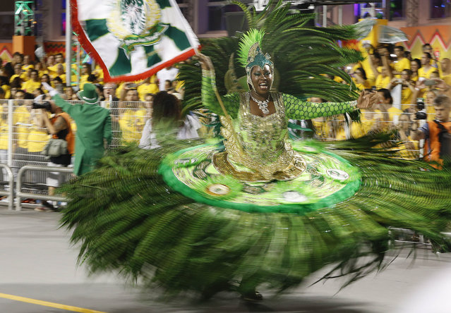 A dancer from the Mancha Verde samba school performs during the Carnival parade at the Sambodromo in Sao Paulo, Brazil, Friday, February 13, 2015. (Photo by Andre Penner/AP Photo)