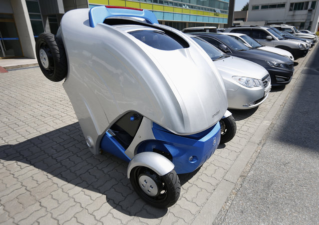 """Armadillo-T, a foldable electric vehicle, folds up its rear at the Korea Advanced Institute of Science and Technology (KAIST) in Daejeon, south of Seoul September 2, 2013.With a click on a smartphone, the experimental """"Armadillo-T"""" electric car made in South Korea will park itself and fold nearly in half, freeing up space in crowded cities. The quirky two-seater, named after the animal whose shell it resembles, may never see production but it is part of a trend of developing environmentally friendly vehicles for urban spaces. Picture taken September 2, 2013. (Photo by Kim Hong-Ji/Reuters)"""
