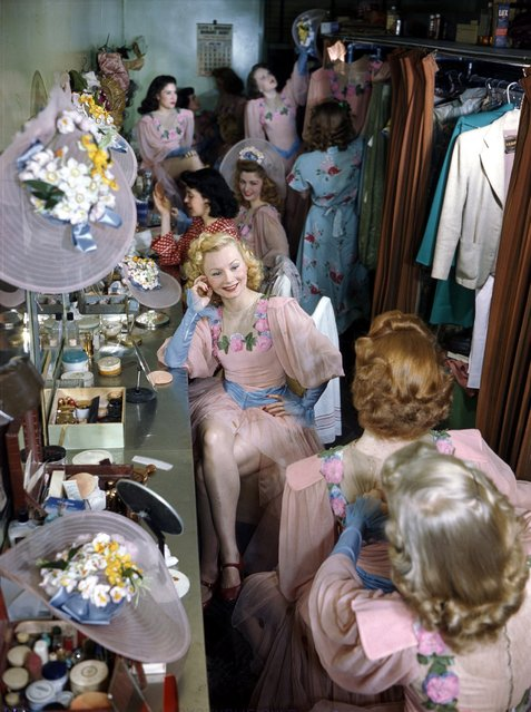 Rockette Olga Burke sits at a dressing table in the Rockettes' dressing rooms, and talks to the girls before a show at the Radio City Music Hall in New York City on July 26, 1949. (Photo by Ivan Dmitri/Getty Images)
