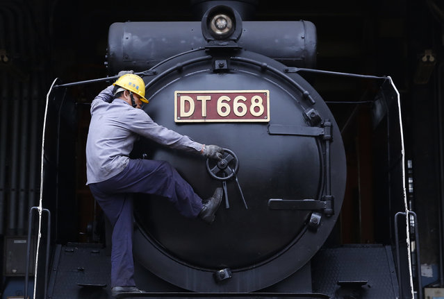 A workman opens the smokebox door of a Japanese-made steam train at a train depot in Changhua, Taiwan, January 13, 2016. (Photo by Olivia Harris/Reuters)