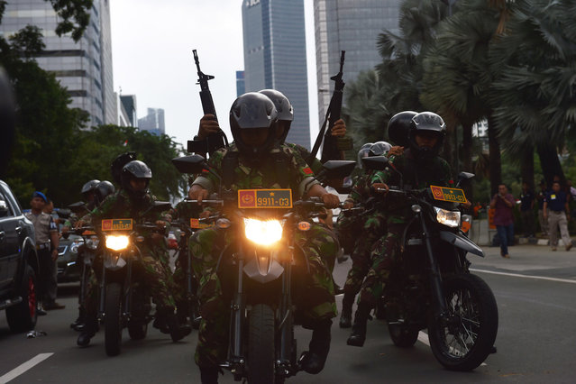 Indonesian armed military patrol the area near cafe after a series of blasts hit Jakarta on January 14, 2016. An attack on Jakarta is over and no more perpertators are at large, police said on January 14, after gunfire and explosions left seven dead in the Indonesian capital. (Photo by Bay Ismoyo/AFP Photo)