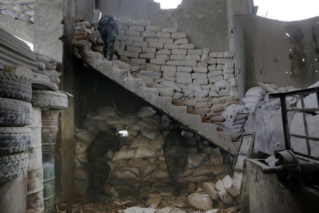 Syrian army soldiers fire their weapons during a battle with rebels at the Ramouseh front line, east of Aleppo, Syria, Monday, December 5, 2016. (Photo by Hassan Ammar/AP Photo)