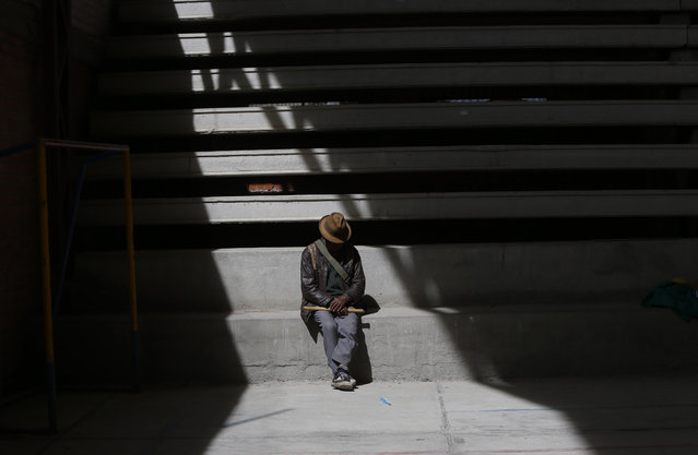 In this February 4, 2105 photo, an Aymara man holding a flute rests in the stands of covered court in El Alto, Bolivia. The man watched elderly Aymara indigenous women play handball. (Photo by Juan Karita/AP Photo)