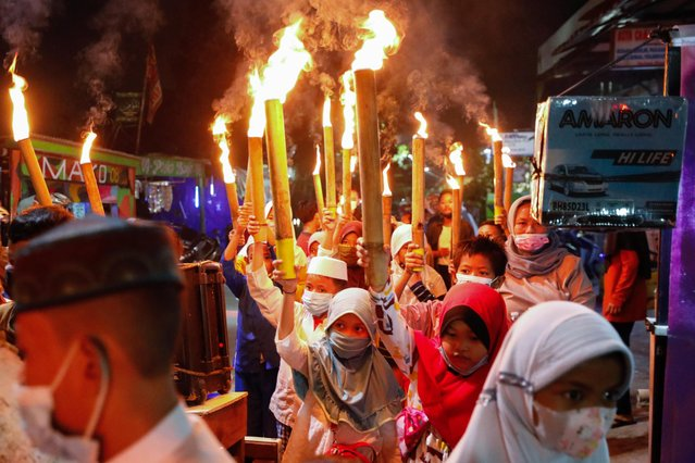 Muslim children carry torches around the neighbourhood during a parade to celebrate Eid al-Fitr, marking the end of the holy fasting month of Ramadan, amid the coronavirus disease (COVID-19) pandemic in Jakarta, Indonesia, May 12, 2021. (Photo by Willy Kurniawan/Reuters)