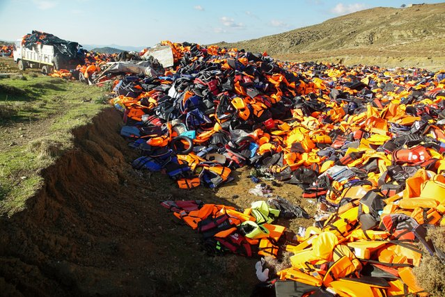 A man unloads a truck filled with various life Jackets at the garbage area in the mountains of Lesbos Island, Greece, January 25, 2016. The buoyancy aides are discarded by migrants and collected from along the shore. More than 850,000 people, most fleeing conflict in Syria and Afghanistan, entered Greece by sea in 2015, according to the UNHCR. (Photo by Mstyslav Chernov/AP Photo)