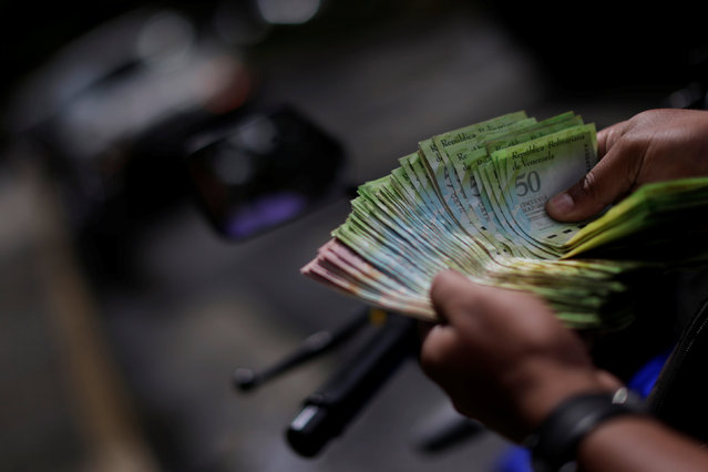 A customer counts his Venezuelan bolivar notes in front of a market in downtown Caracas, Venezuela, December 7, 2016. (Photo by Ueslei Marcelino/Reuters)