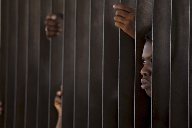 DOMINICAN REPUBLIC: A Haitian woman peeks through a fence surrounding the Ministry of Interior and Police while waiting to register in Santo Domingo, June 16, 2016. (Photo by Ricardo Rojas/Reuters)