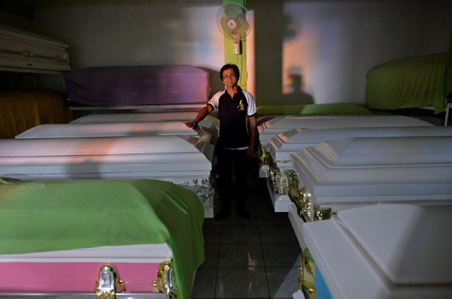 """Orly Fernandez, 64, operational manager at Eusebio Funeral Services poses for a photograph next to empty coffins in Navotas city, Metro Manila, Philippines October 30, 2016. Fernandez lives in the funeral parlour. """"Before maybe we picked up one body per day, now we get around two or three bodies a day"""", he said. (Photo by Ezra Acayan/Reuters)"""
