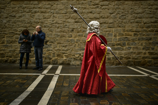 A man dressed in ancient regional costume walks along a street of the old city while taking part in a procession in honor of Saint Saturnino, in Pamplona, northern Spain, Thursday, November 29 2018. (Photo by Alvaro Barrientos/AP Photo)