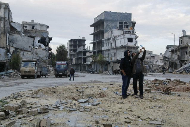 Civilians take pictures of themselves at the damaged al-Halwaniyeh roundabout in Aleppo January 2, 2015. (Photo by Hosam Katan/Reuters)