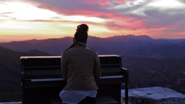 In this March, 2015 photo, a person sits at an upright piano that had been hauled up to Topanga Lookout in the Santa Monica Mountains in Calabasas, Calif. For a couple of days last week, a Southern California hilltop was alive with the sound of mystery. (Photo by Michael Flotron/AP Photo)