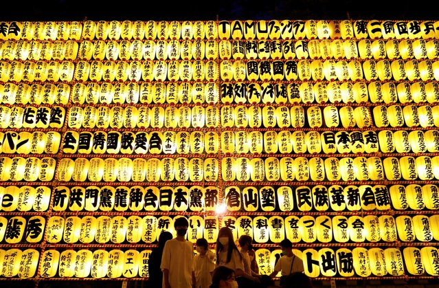 Visitors wearing protective face masks look at thousands paper lanterns during the Mitama Festival at the Yasukuni Shrine, where more than 2.4 million war-dead are enshrined, during a fourth coronavirus state of emergency for the Tokyo capital ahead of the opening of Tokyo 2020 Olympic Games in Tokyo, Japan on July 13, 2021. (Photo by Issei Kato/Reuters)