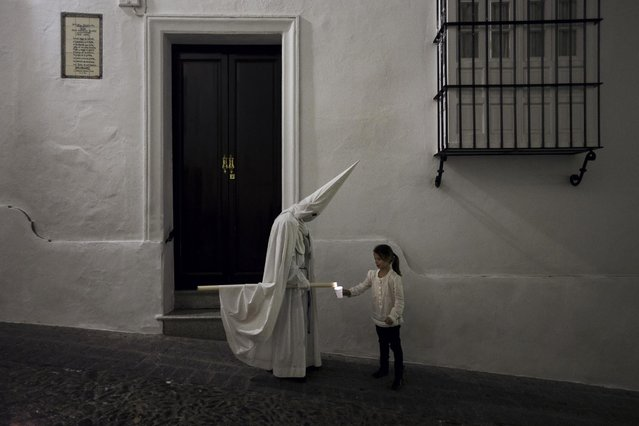 "A girl collects wax from a penitent large candle during the Holy Week procession of  ""Nuestro Senor Atado a la Columna, Maria Santisima de la Paz y San Juan Evangelista"" in Arcos de la Frontera, Spain, Tuesday, March 31, 2015. (Photo by Daniel Ochoa de Olza/AP Photo)"