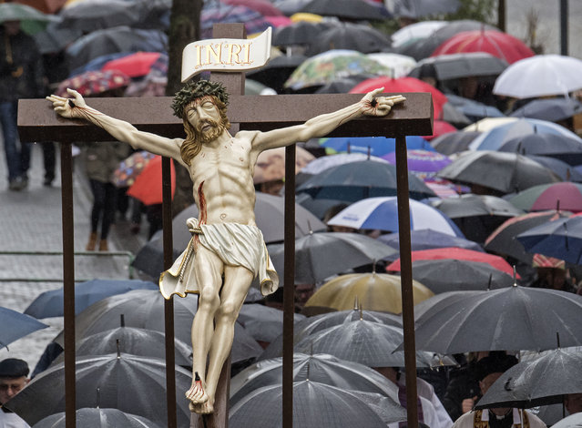 Believers carry a cross during heavy rain at the Palm Sunday procession in the old town of Heiligenstadt, central Germany, Sunday, March 29, 2015. The procession takes place with life-size figures from the Passion of Christ and under the presence of several thousand people. (Photo by Jens Meyer/AP Photo)