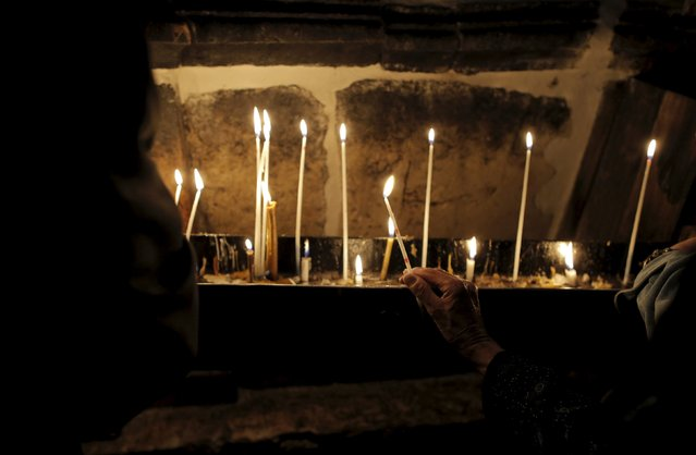 A Christian worshipper holds a candle during the Catholic Easter procession in the Church of the Holy Sepulchre in Jerusalem's Old City April 5, 2015. (Photo by Ammar Awad/Reuters)
