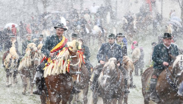 Local residents dressed in traditional Bavarian clothes of the region ride  during  heavy snowfall to get blessing for men and beast at the traditional Georgi  (St. George) horse riding procession on Easter Monday in Traunstein, southern Germany, Monday, April 6, 2015. (Photo by Matthias Schrader/AP Photo)