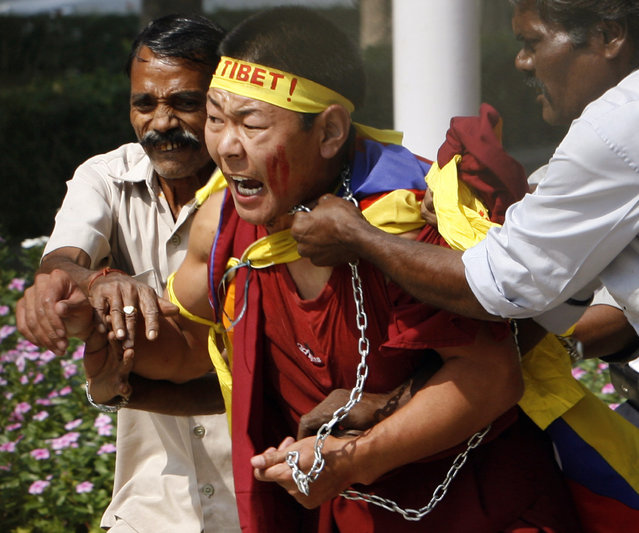 A Tibetan exile is led out by guards from inside the Chinese Embassy compound in New Delhi,October 2007. (Photo by Desmond Boylan/Reuters)
