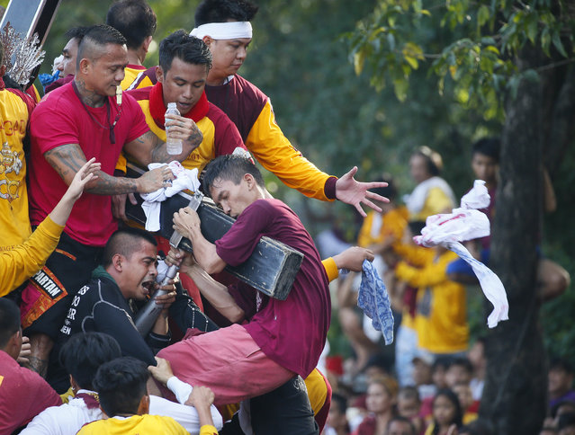 Filipino Roman Catholic devotees climb the carriage to kiss and rub with their towels the image of the Black Nazarene to celebrate its feast day Monday, January 9, 2017 in Manila, Philippines. (Photo by Bullit Marquez/AP Photo)