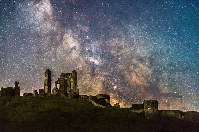The galactic centre of the Milky Way glows brightly in the clear night sky as it rises from behind the ruins of Corfe Castle in Dorset, United Kingdom on April 18, 2021. (Photo by Graham Hunt/Alamy Live News)