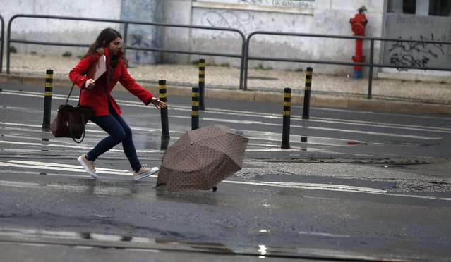 A woman tries to catch her umbrella after it was blown away by the wind in downtown Lisbon February 3, 2015. (Photo by Rafael Marchante/Reuters)