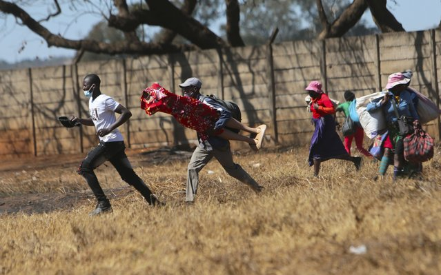 Zimbabwean vendors flee from the police after they were chased away from selling their wares from undesignated areas due to COVID-19 restrictions in Harare, Thursday July 29, 2021. (Photo by Tsvangirayi Mukwazhi/AP Photo)