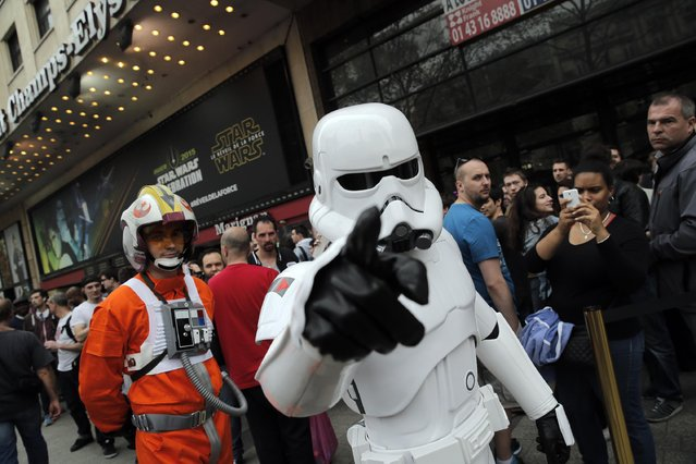 A man dressed as a Stormtrooper walks past people as they queue to attend the steaming of Star Wars Celebration from the Anaheim Convention Center in California, in Paris, France, Thursday, April 16, 2015. Star Wars Celebration is a fan gathering to celebrate the release of a Star Wars franchise movie, panel discussions, and exclusive reveals. (Photo by Christophe Ena/AP Photo)