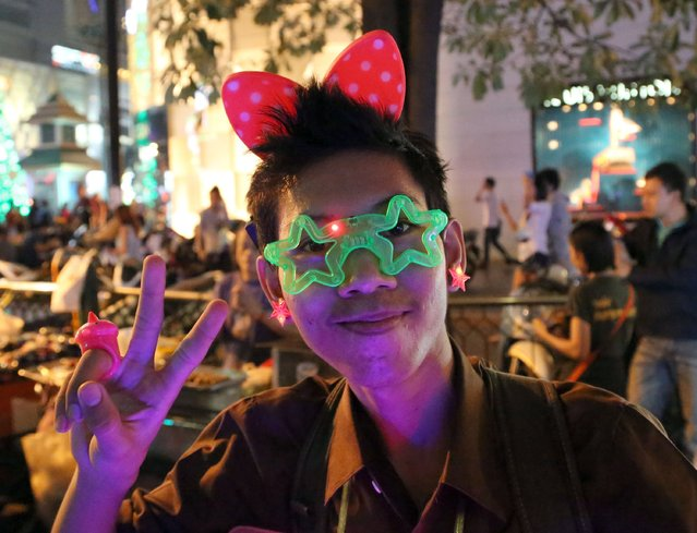 A Thai youth poses for a photograph up as he joins with others to celebrate the New Year in Bangkok, Thailand, Tuesday, December 31, 2013. (Photo by Apichart Weerawong/AP Photo)