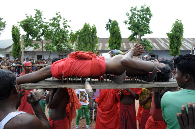 A Hindu devotee lies on a bed of nails as he is carried past spectators during the ritual of Shiva Gajan at Pratapgarh village in Agartala, the capital of northeastern state of Tripura on April 14, 2015.  Devotees believe that by enduring the pain, Shiva, the Hindu god of destruction, will grant their prayers. (Photo by Arindam Dey/AFP Photo)