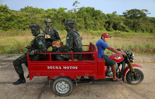 Brazilian army forces soldiers take a ride at the border of Brazil with Colombia during a training which aims to increase the security along borders, in Vila Bittencourt, Amazon State, Brazil, January 18, 2017. (Photo by Adriano Machado/Reuters)