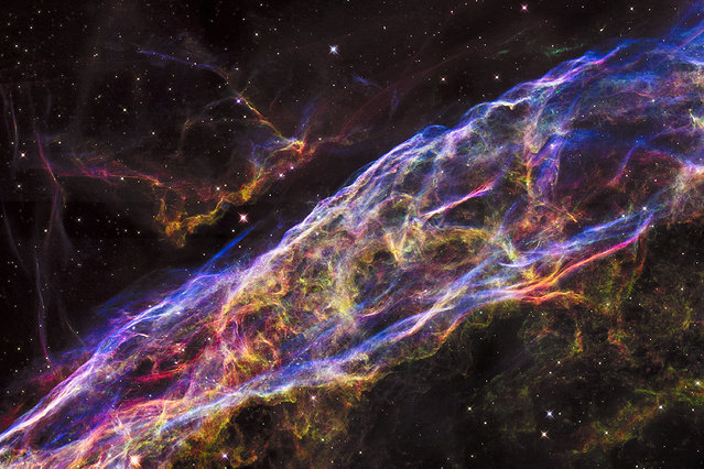 A small section of the expanding remains of the Veil Nebula, a massive star that exploded about 8,000 years ago. The entire nebula is 110 light-years across, covering six full moons on the sky as seen from Earth, and resides about 2,100 light-years away in the constellation Cygnus, the Swan. (Photo by Reuters/NASA/ESA/Hubble)
