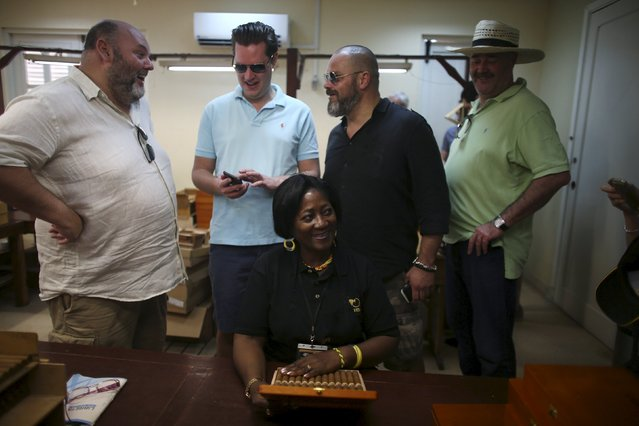 Tourists chat at the Cohiba Tobacco factory during a visit in Havana, March 3, 2016. (Photo by Alexandre Meneghini/Reuters)