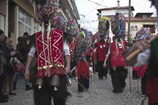 Participants wearing goat hides with bells around their waists and masks that include a meter tall, ribbon-covered formation topped with a foxtail participate in a Clean Monday festival at the village of Sohos, Monday, March 11, 2019. The procession is one of a great variety of customs across Greece. Celebrating the beginning of Lent it is rooted in the ancient past, many, experts believe, celebrating fertility. (Photo by Petros Giannakouris/AP Photo)