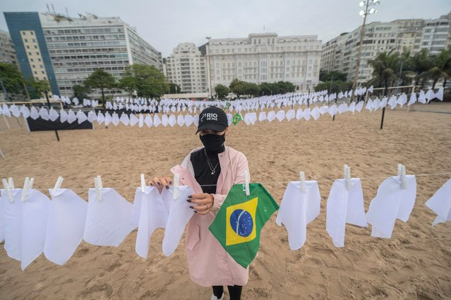 A demonstrator from the Rio de Paz human rights activist group hangs white flags symbolizing the deaths of almost 600,000 Brazilian to the novel coronavirus COVID-19, at Copacabana beach in Rio de Janeiro, Brazil, on October 8, 2021. The group protested against the rising figures of COVID-19 deaths in the country which is about to surpass 600,000 mortal victims. (Photo by Mauro Pimentel/AFP Photo)