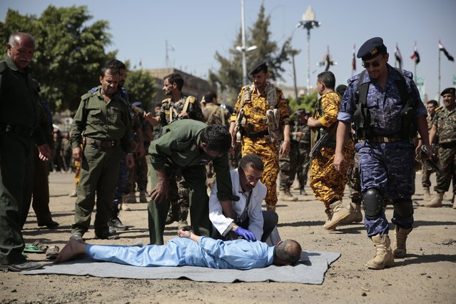 Policemen prepare a man convicted of involvement in the killing of a senior Houthi official Saleh al-Samad, to be executed at Tahrir Square in Sanaa, Yemen Saturday, September 18, 2021. Yemen's Houthi rebels Saturday said they executed nine people for their alleged involvement in the killing of a senior Houthi official in an airstrike by the Saudi-led coalition more than three years ago. (Photo by Hani Mohammed/AP Photo)