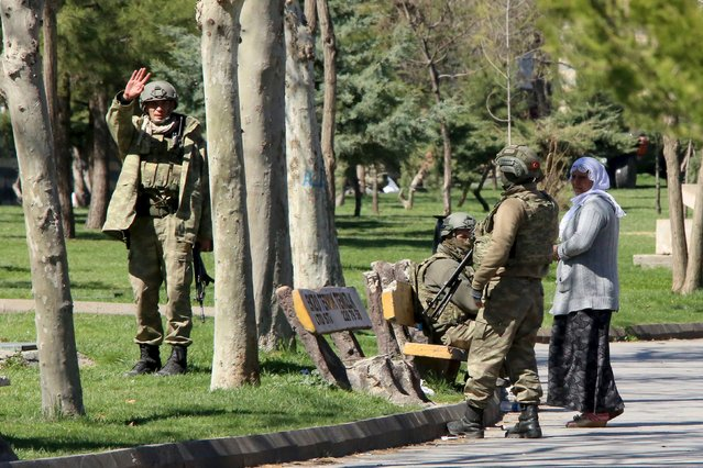 Turkish soldiers stand at a park in Baglar district, which is partially under curfew, in the Kurdish-dominated southeastern city of Diyarbakir, Turkey March 17, 2016. (Photo by Sertac Kayar/Reuters)