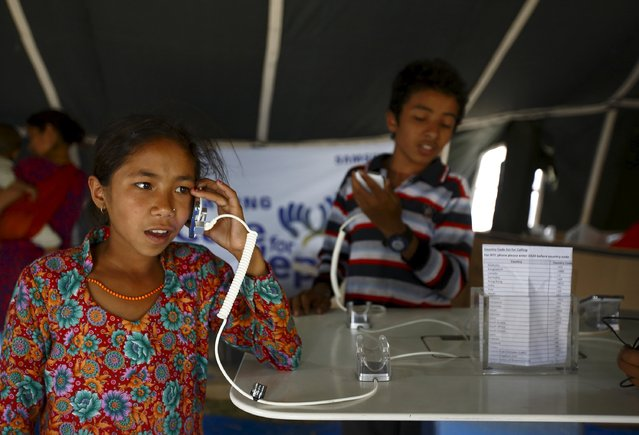 A girl speaks with her mother on a phone inside a temporary phone booth built by Samsung to provide free service to earthquake victims in Kathmandu May 6, 2015. (Photo by Navesh Chitrakar/Reuters)