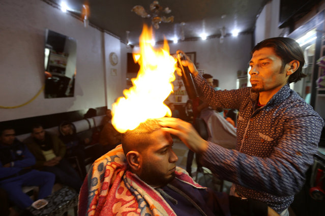 "Palestinian barber Ramadan Odwan styles and straightens the hair of a customer with fire at his salon in Rafah, in the southern Gaza Strip February 2, 2017. In Ramadan Odwan's barbershop in Gaza, hair isn't just blow-dried, it's blowtorch-dried. ""People have gone crazy about it, many people are curious to go through the experience and they are not afraid"", he told Reuters. ""People here love adventures"". Odwan, 37, is not the first stylist in the world to use flame to straighten hair, but his craft is unique in the Gaza Strip. In his salon in the southern Gaza town of Rafah, Odwan applied what he described as a protective liquid coating to a customer's hair – he declined to disclose its contents – before aiming for the head and pressing the button on a small blowtorch. ""I control how long I apply fire, I keep it on and off for 10 seconds or 15 seconds. It is completely safe and I have not encountered any accident since I started it two months ago"", Odwan added. Odwan charges 20 shekels ($5.20) for a haircut and fire-straightening. A barber for the past 18 years, he said part of the reason he uses the technique is to show that Palestinian barbers are as ""professional as those out there around the world"". (Photo by Ibraheem Abu Mustafa/Reuters)"
