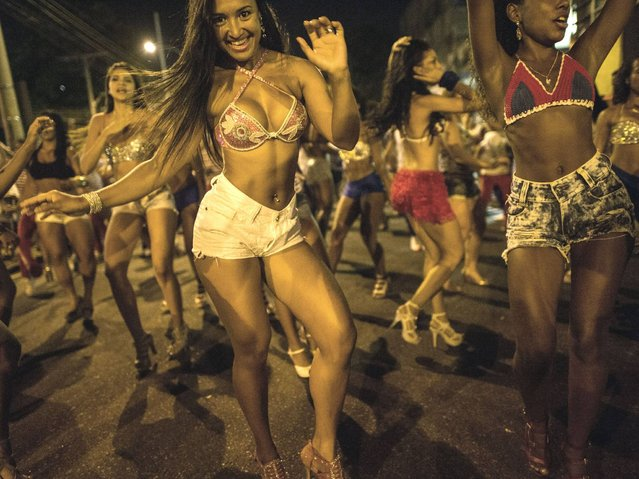 Dancers of Uniao da Ilha do Governador samba school perform during their rehearsal on a street in Rio de Janeiro, Brazil on Februrary 12, 2014. Rio's carnival will be held on March 2 and 3, 2014. (Photo by Yasuyoshi Chiba/AFP Photo)