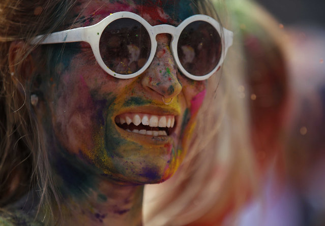 A woman with coloured powder smeared on her face smile as she celebrates Holi, the Festival of Colours, in Kathmandu, Nepal, March 22, 2016. (Photo by Navesh Chitrakar/Reuters)