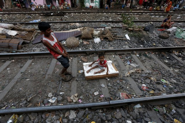 Ratan Mandal, 10, pulls three-year-old Bubai Tati, as he sits on a broken box on a railway track in a slum area in Kolkata, India, March 13, 2016. (Photo by Rupak De Chowdhuri/Reuters)