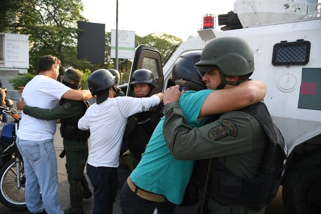 Supoprters of self-proclaimed acting president Juan Guaido hug members of the security forces in Caracas on April 30, 2019. Venezuelan opposition leader and self-proclaimed acting president  Juan Guaido said on Tuesday that troops had joined his campaign to oust President Nicolas Maduro as the government vowed to put down what it said was an attempted coup. (Photo by Yuri Cortez/AFP Photo)