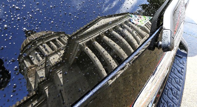 The Legislative Building is reflected through raindrops on the rear window of a vehicle Friday, April 24, 2015 at the Capitol in Olympia, Wash. (Photo by Ted S. Warren/AP Photo)
