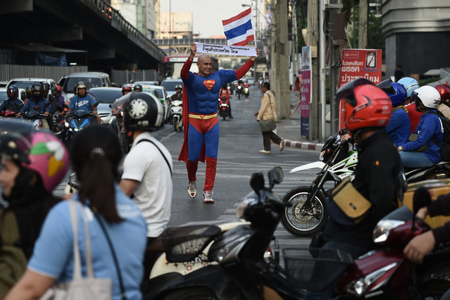 """Thai-German national David Pfizenmaier walks through a traffic intersection holding a sign encouraging Thais to vote in the upcoming election in Bangkok on March 21, 2019. Dressed in a Superman suit with red cape flowing behind him, a sweaty David Pfizenmaier jogs through Bangkok's standstill traffic and stops to unfurl a sign. The 40-year-old Thai-German said on March 21 he is not campaigning for a specific party, but is instead on a mission to boost turnout, especially among younger voters, """"because the military government is not the solution for the long term"""". (Photo by Lillian Suwanrumpha/AFP Photo)"""