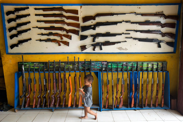 The son of the owner of an air rifle shop walks past air rifles on display at the shop nearby dozens of small air rifle workshops on March 4, 2014 in Cipacing, Indonesia.  The small village is known for its gunsmiths who, despite smaller sales due to competition from big international factories, still make thousands of air rifles annually with most of them made in small back garden operations. (Photo by Ed Wray/Getty Images)