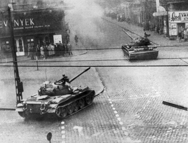 Soviet-built tanks wheel into action in a smoke-filled Budapest street in Hungary's flaring revolution against communist satellite government, October 27, 1956. Citizens stand close to building fronts to stay out of the line of fire. Many Hungarian Army units reportedly have gone over to the rebels in fighting against police and units of the Soviet Red Army. (Photo by AP Photo)