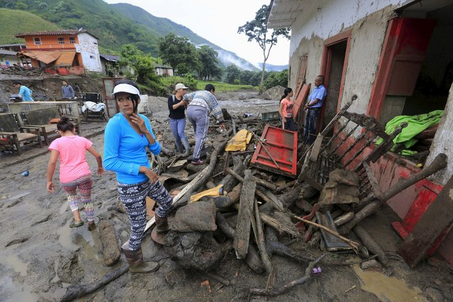 Residents stand in front of the ruins of a house, after a landslide close to the municipality of Salgar in Antioquia department, Colombia May 19, 2015. (Photo by Jose Miguel Gomez/Reuters)
