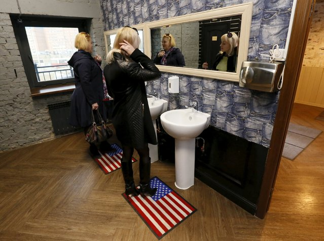 "Visitors stand on rugs depicting the U.S. flag in a toilet at the ""President Cafe"" in Krasnoyarsk, Siberia, Russia, April 7, 2016. (Photo by Ilya Naymushin/Reuters)"