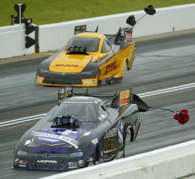 Funny Car drivers Jack Beckman, bottom, and Dale Warshem deploy their parashoots after racing in the semifinals of the 2015 NHRA Kansas Nationals on Sunday, May 24, 2015, at Heartland Park in Topeka, Kan. (Photo by Chris Neal/The Topeka Capital-Journal via AP Photo)