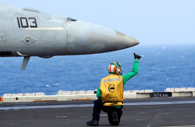 A flight deck crew gives a hand signal to the pilot of a U.S. Navy F18 fighter jet on aircraft carrier USS Carl Vinson during a FONOPS (Freedom of Navigation Operation Patrol) in South China Sea, March 3, 2017. (Photo by Erik De Castro/Reuters)